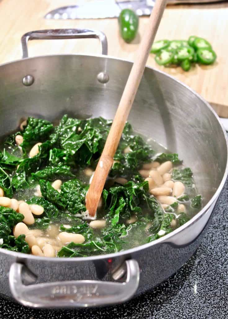 Tuscan Kale and Cannellini Bean Soup on stove cooking with wooden spoon