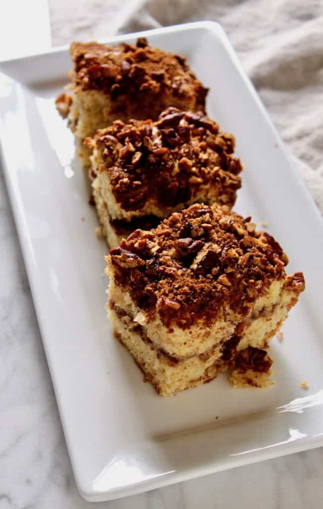 Overhead photo of three pieces of coffee cake on white plate.