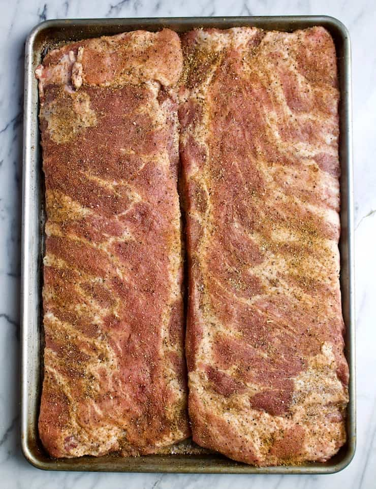 Two slabs of pork spareribs with dry rub, ready for grill.