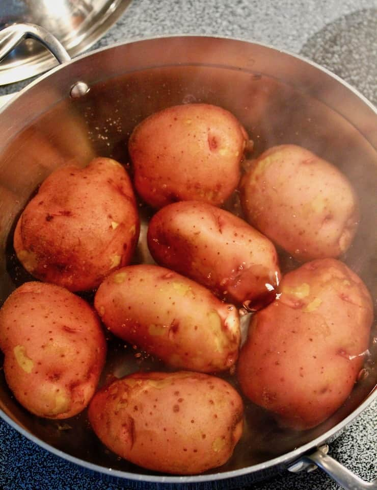 German Potato Salad, red potatoes cooking in boiling water.