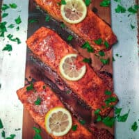 Finished cedar planked salmon garnished with lemon slices and chopped parsley.