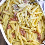 Baked penne with prosciutto and Parmesan cream in casserole dish.