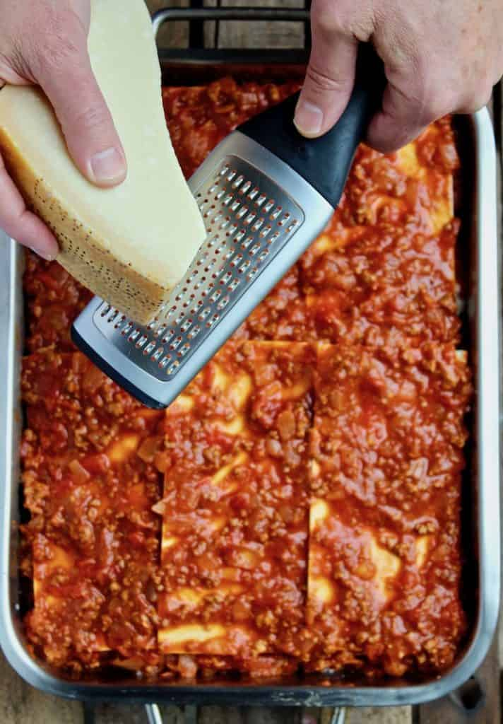 Mom's Lasagna, grating Parmesan over top of lasagna before baking