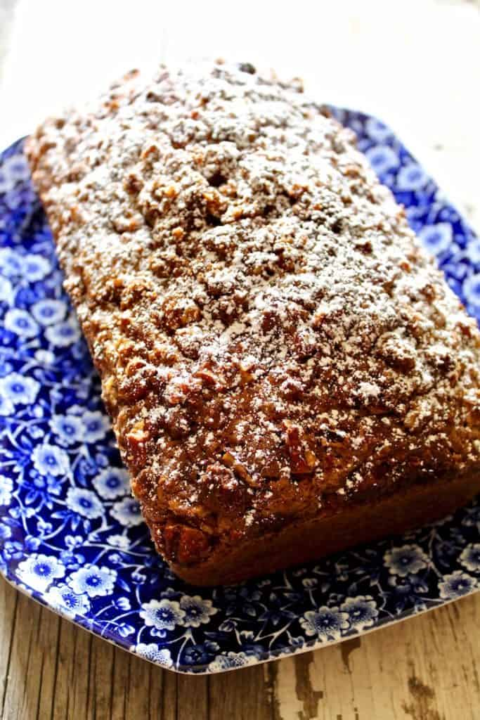 Loaf of pumpkin bread dusted with powdered sugar on blue serving platter.