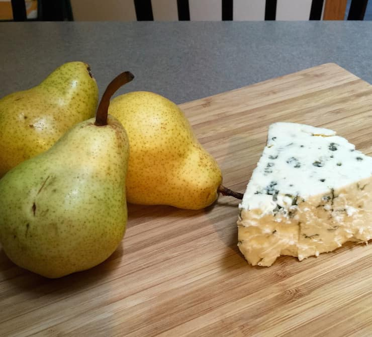 Three pears and wedge of blue cheese on cutting board.