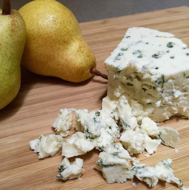 Crumbled blue cheese on cutting board.