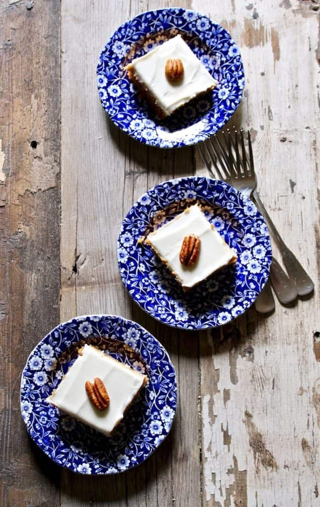 Overhead photo of three blue serving plates of pumpkin bars topped with a pecan.
