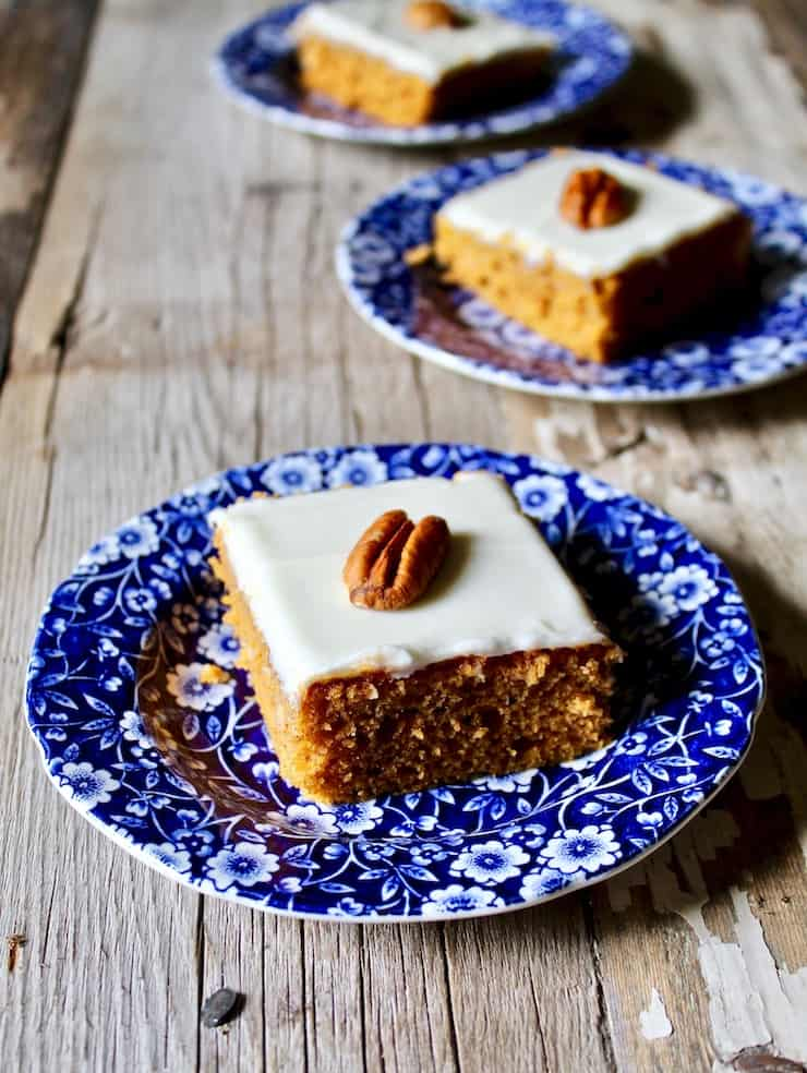 Close up of pumpkin bars with pecan on top on blue serving plate.