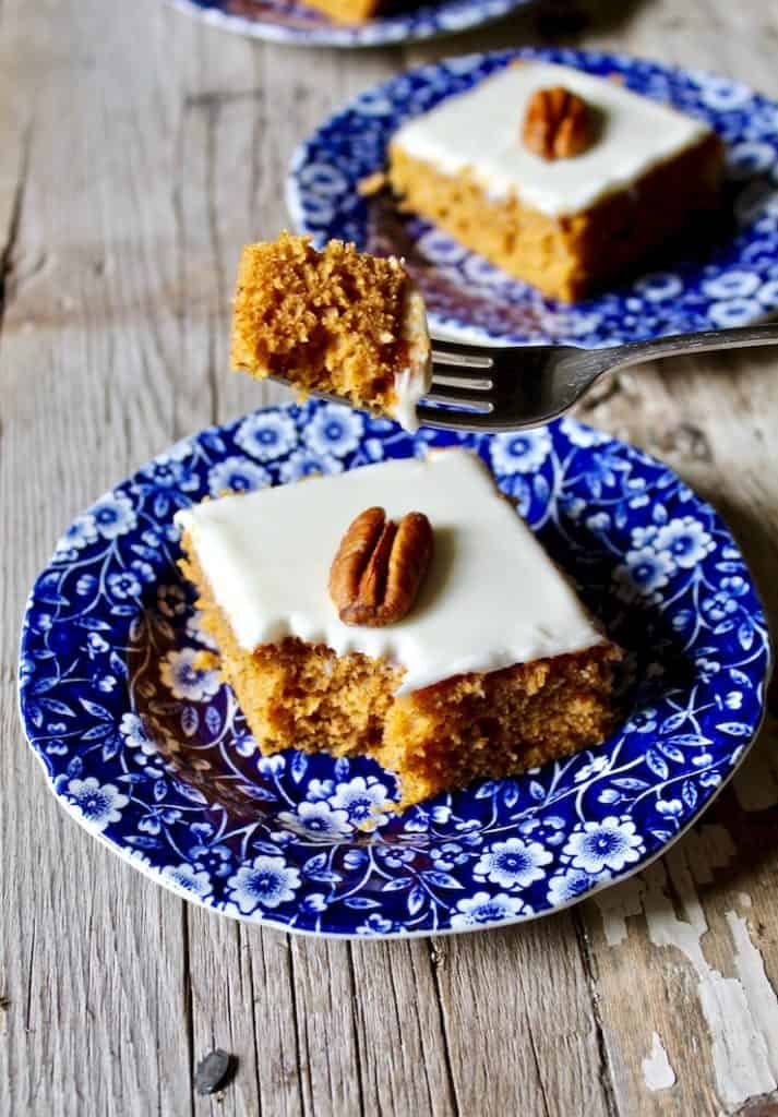 Pumpkin bar on blue plate with forkful of cake.