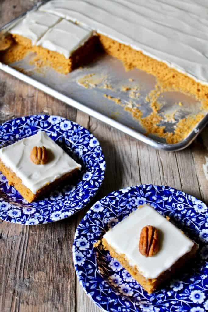 Pumkin bars on plates with frosted sheet cake pan in background.