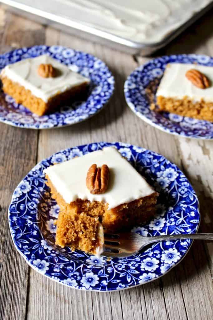 Pumpkin bars on blue serving plates topped with pecans.