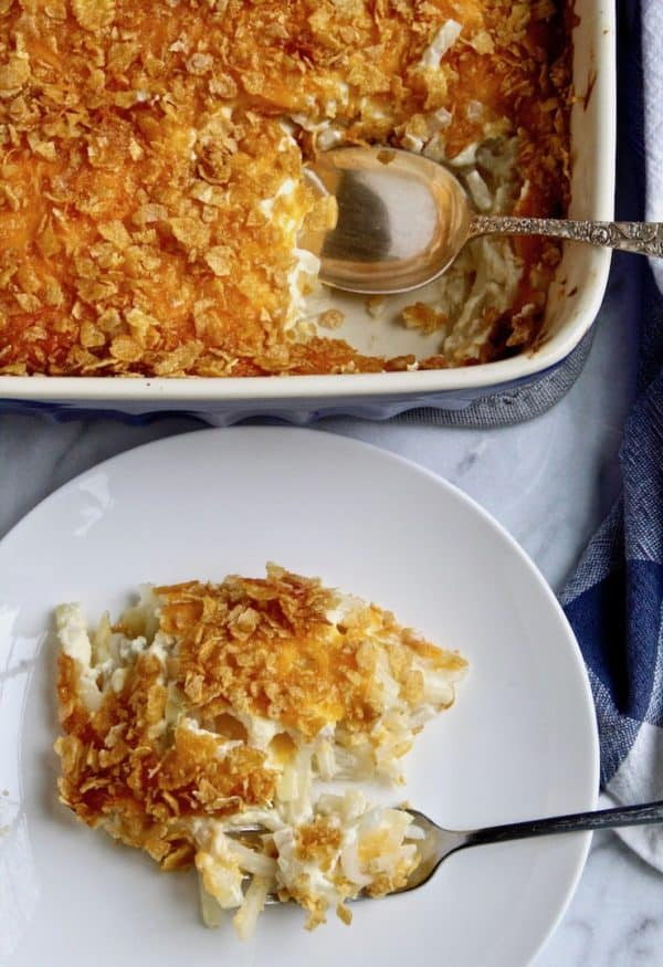 Cheesy Potatoes, on a serving plate with fork, casserole in background