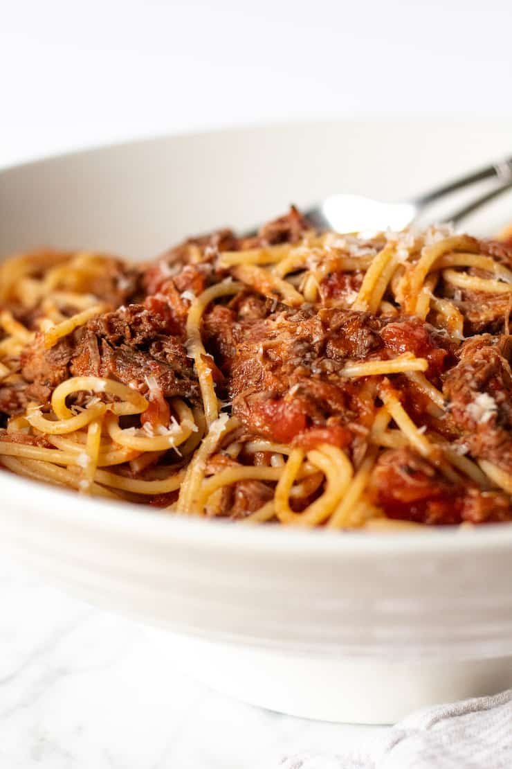 Sunday gravy tossed with spaghetti in serving bowl.