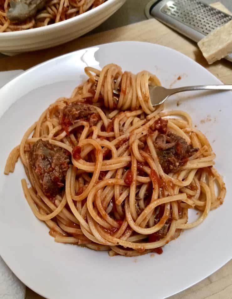 Sunday gravy and pasta swirled on fork on white dish.