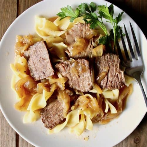 Beer-Braised Beef and Onions, on plate with egg noodles and fork.