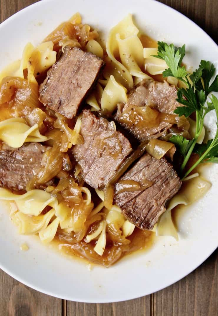 Beer-Braised Beef and Onions, on plate with egg noodles.