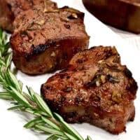 Lamb chops on white platter.