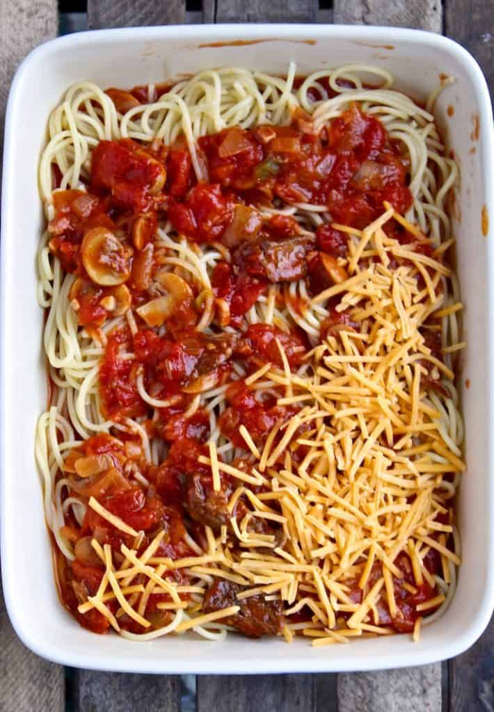 Overhead of layering casserole with sauce, spaghetti and cheese.
