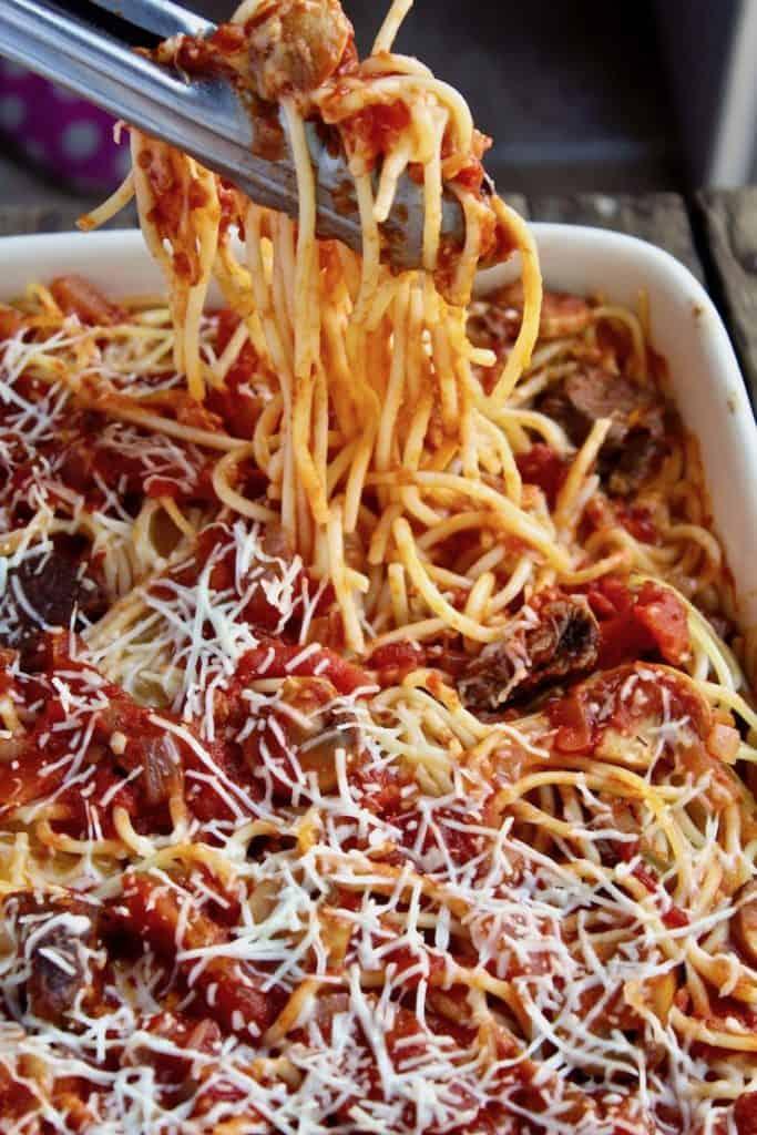 Tongs holdong spaghetti over casserole dish.