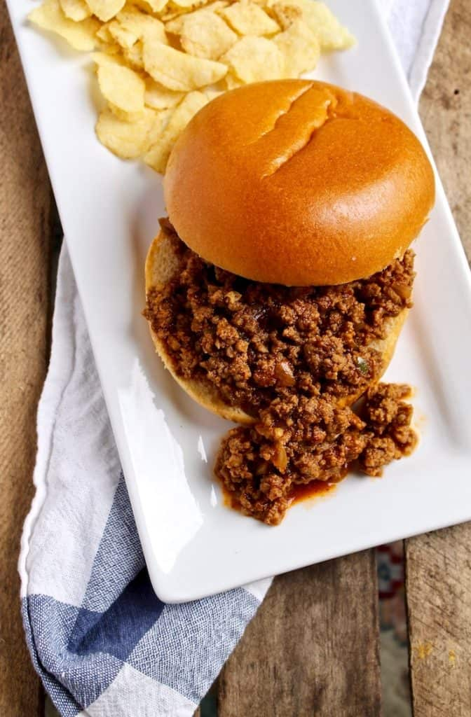 Sloppy Joes, sandwich on white rectangular plate with chips.