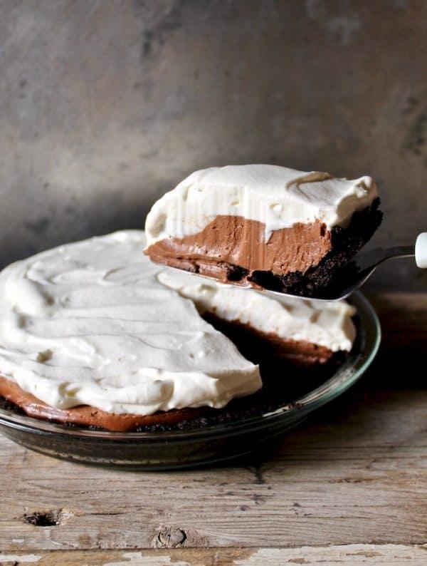 Slice of chocolate cream pie held above the pie