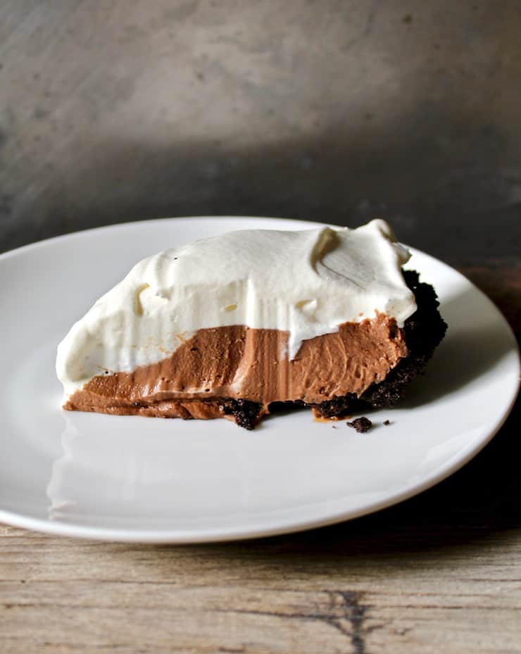 Slice of chocolate cream pie on white plate.