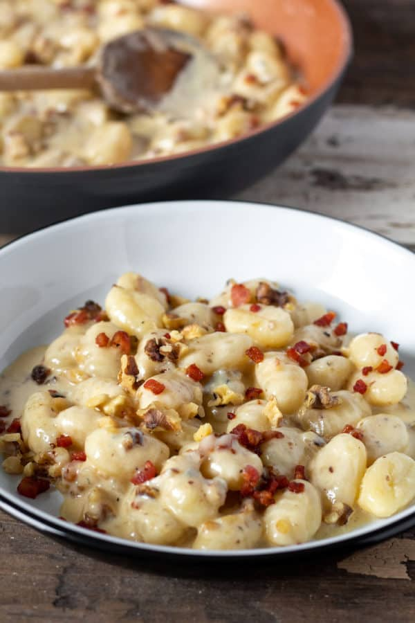 Gnocchi with gorgonzola, walnuts and pancetta on serving plate.