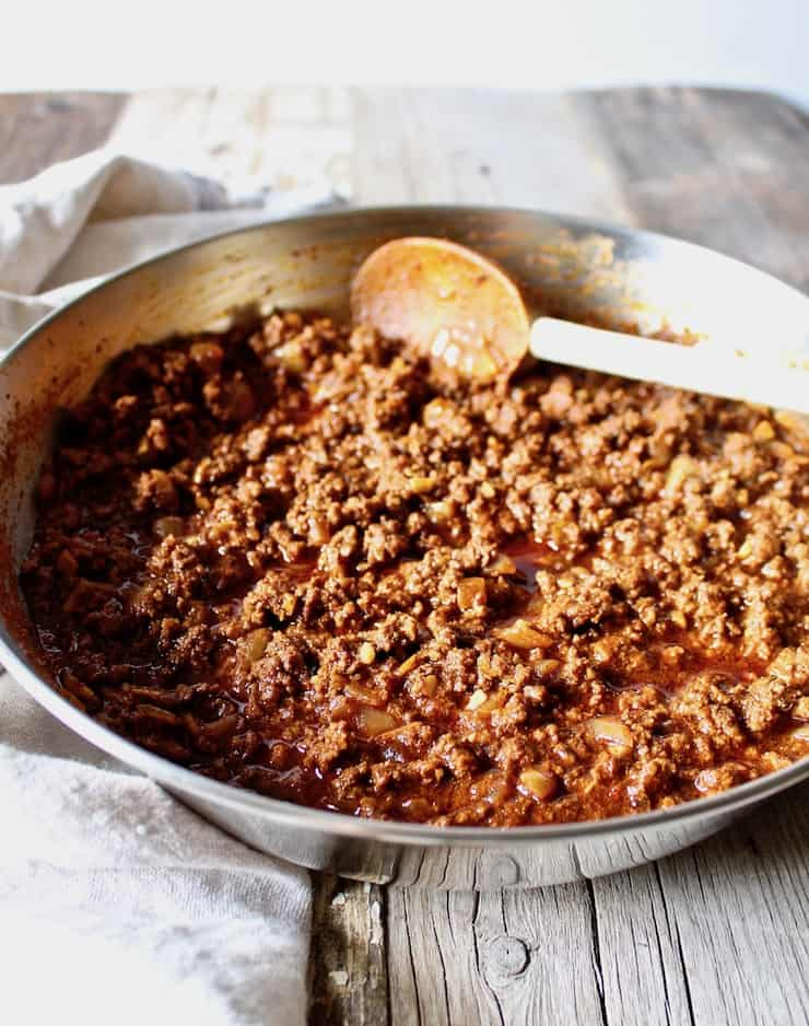 Ground beef taco meat, in pan with wooden spoon.
