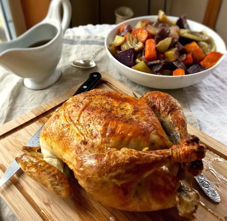 Roast chicken on carving board with bowl of vegetables.