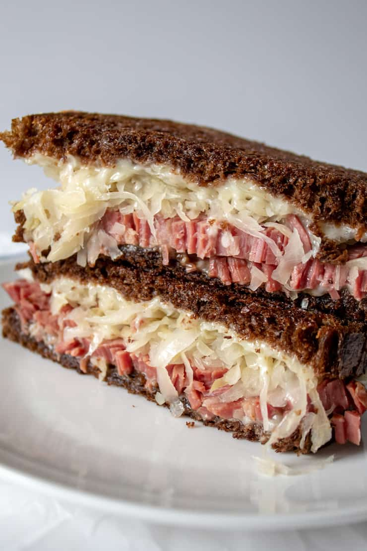 Reubens, close up of grilled Reuben sandwich, stacked.