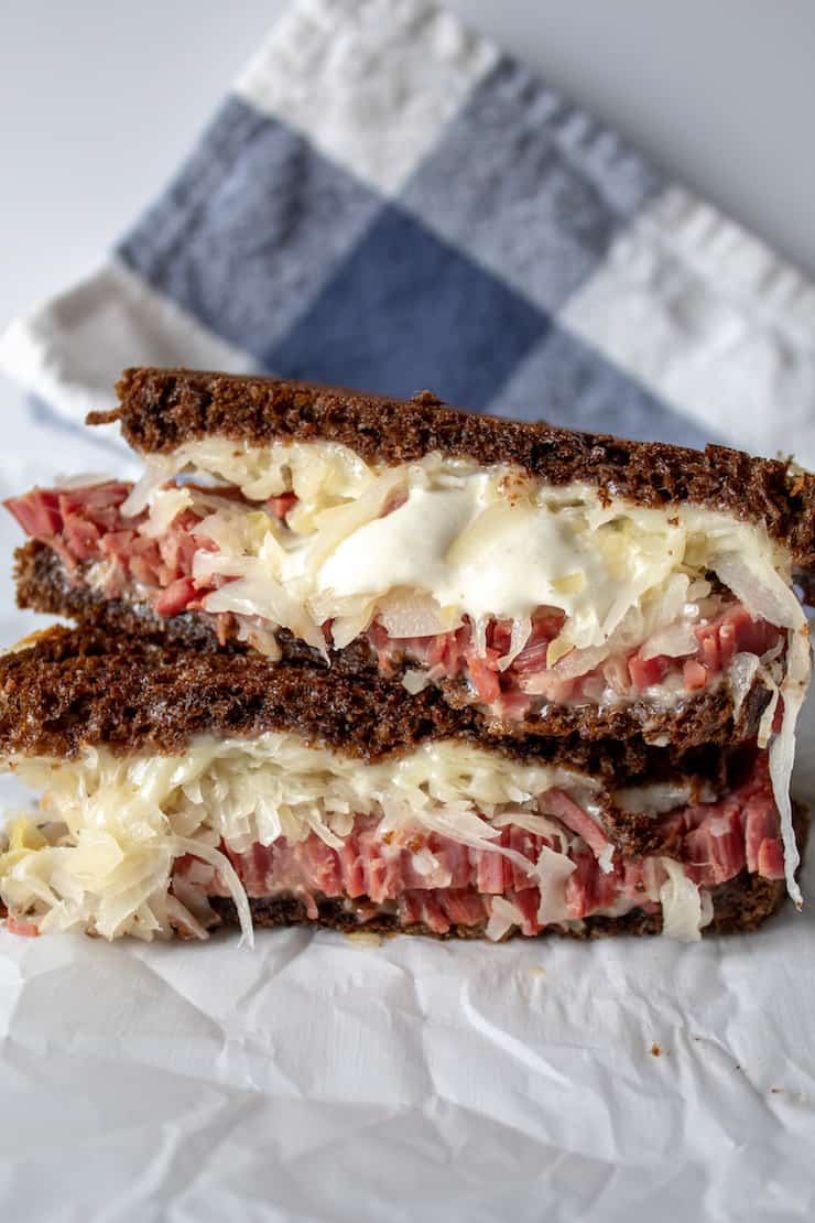 Reubens, grilled Reuben sandwich cut in half and stacked.