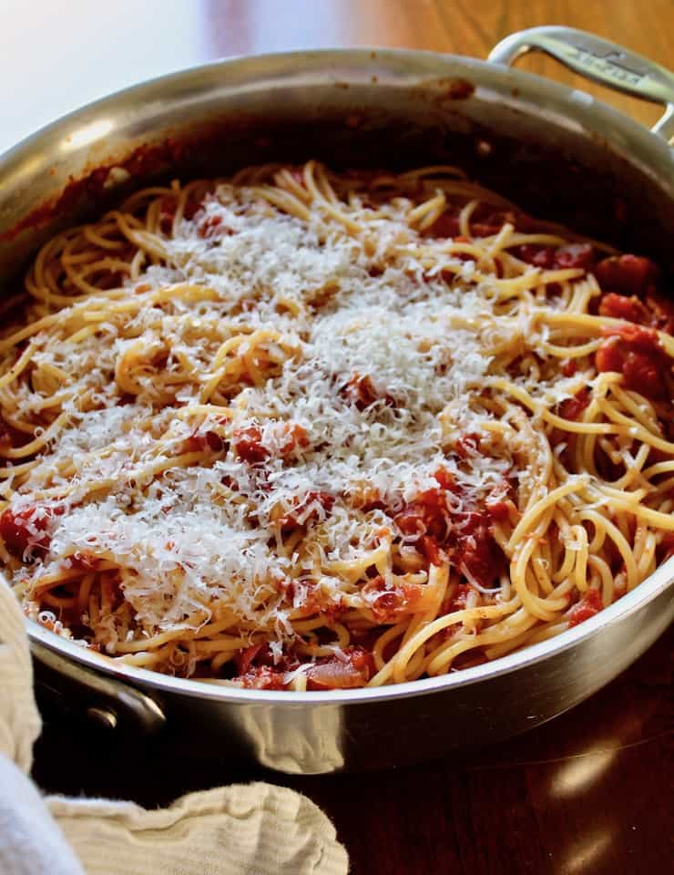 Spaghetti with Bacon Sauce, in skillet with grated cheese on top