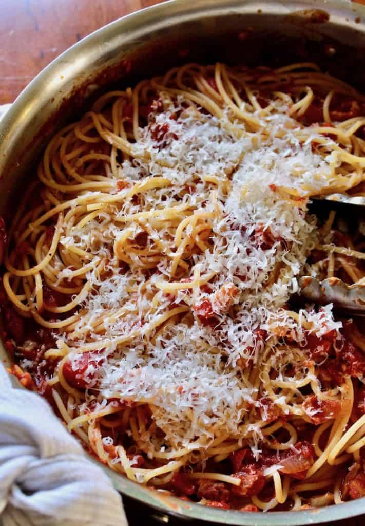 Spaghetti with Bacon Sauce, in skillet with grated cheese and tongs