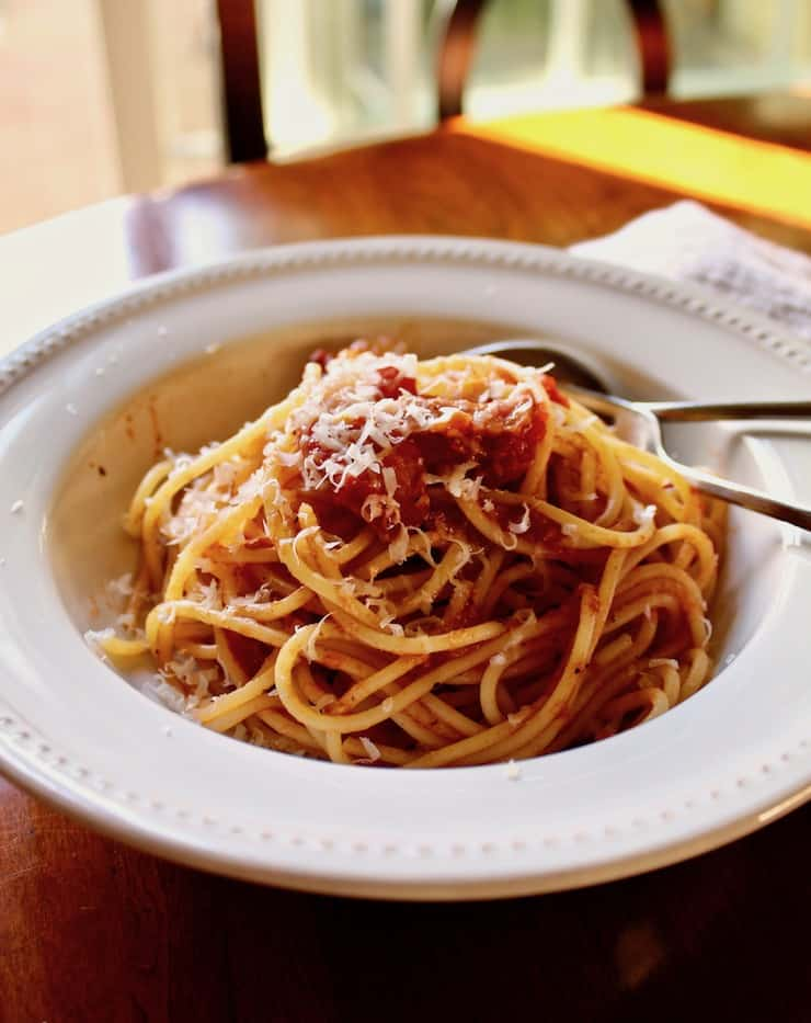 Spaghetti with Bacon Sauce, in bowl with spoon and fork.
