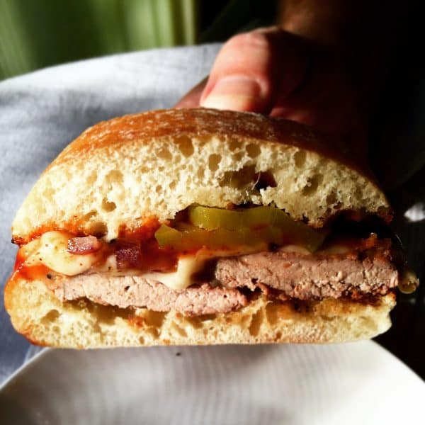 Grilled Pork Tenderloin Sandwich, holding sandwich to show filling