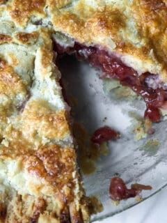 Overhead of cherry pie with piece missing, showing flaky crust and filling.
