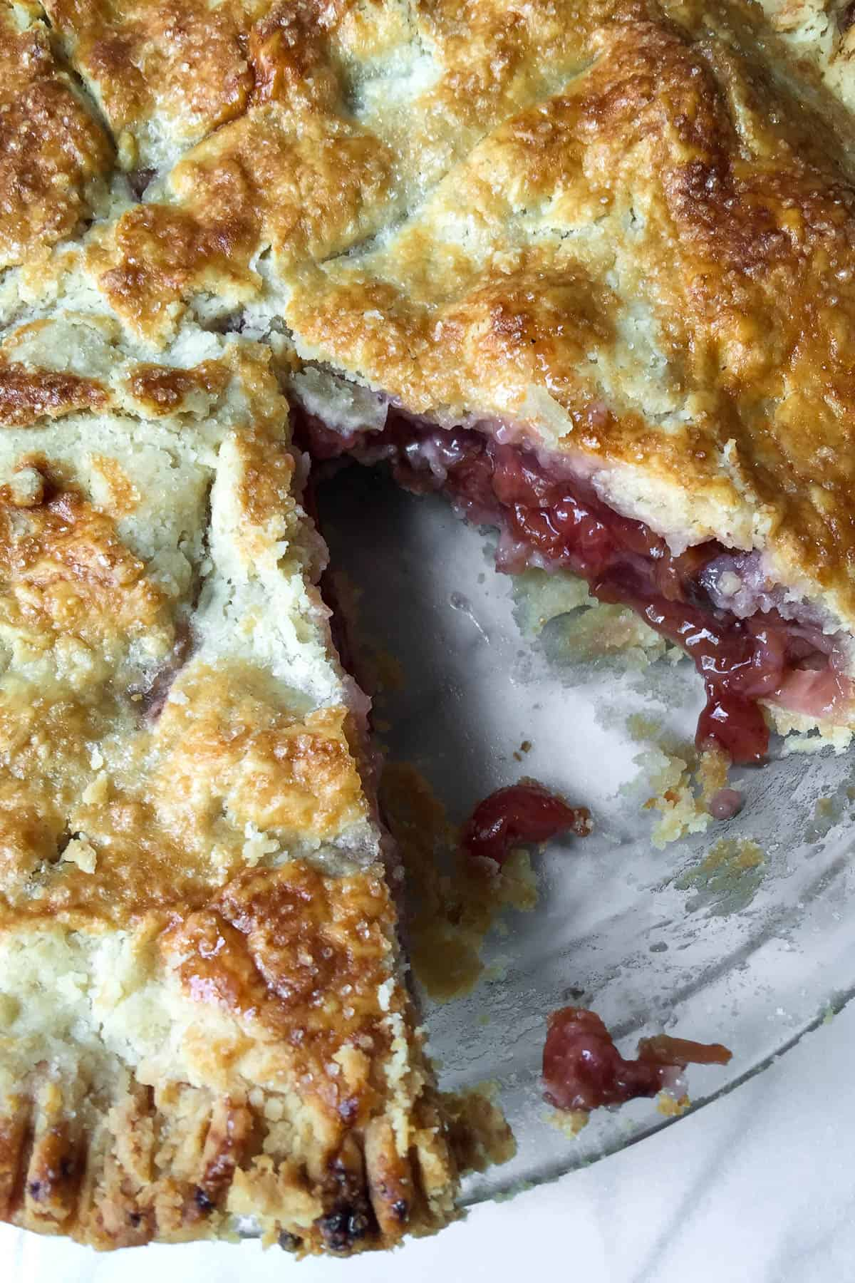 Close up of cherry pie with a piece cut out.