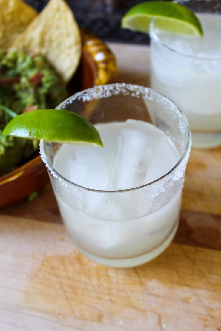Margarita in glass with lime wedge and salted rim.