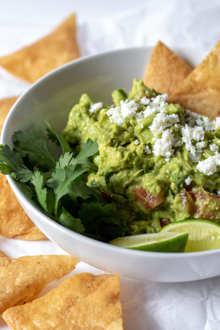 Guacamole in white bowl with crumbled fresh cheese and homemade chips.