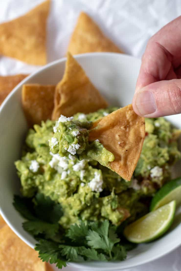 Hand dipping a chip in guacamole.