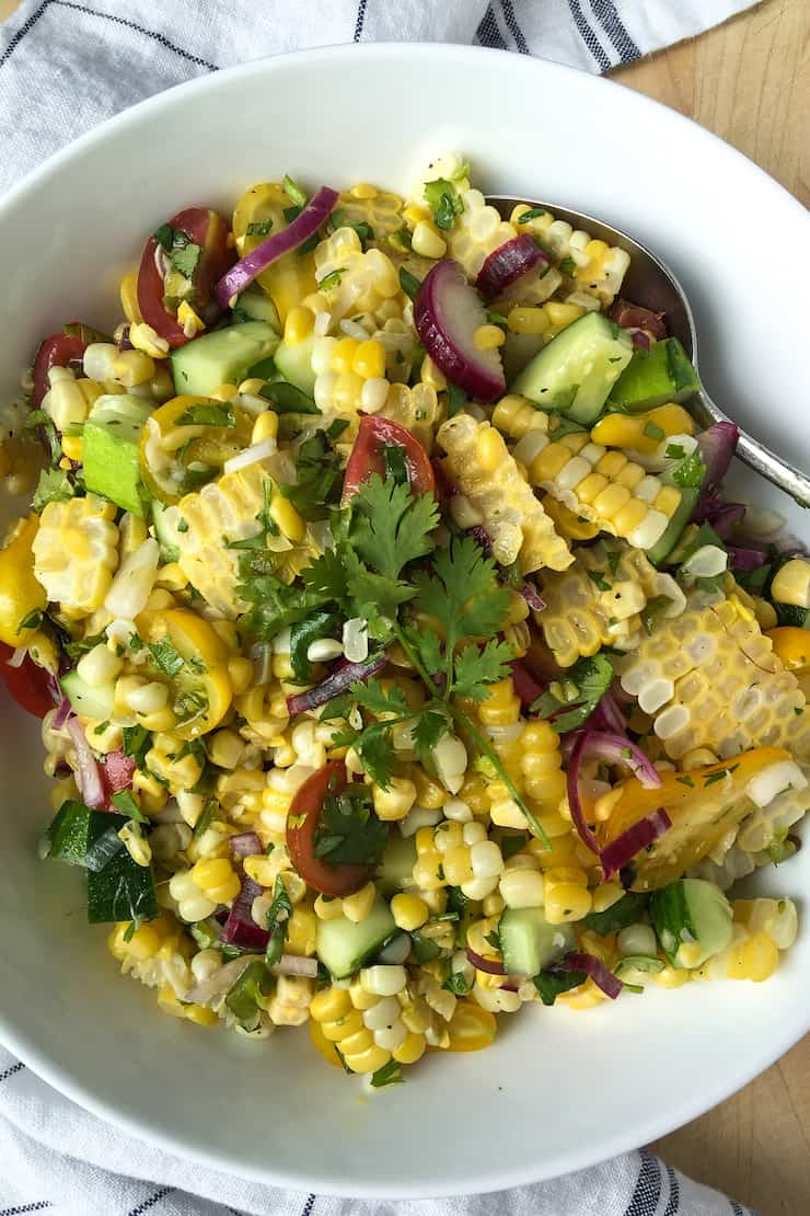 Grilled corn salad in serving bowl with spoon.