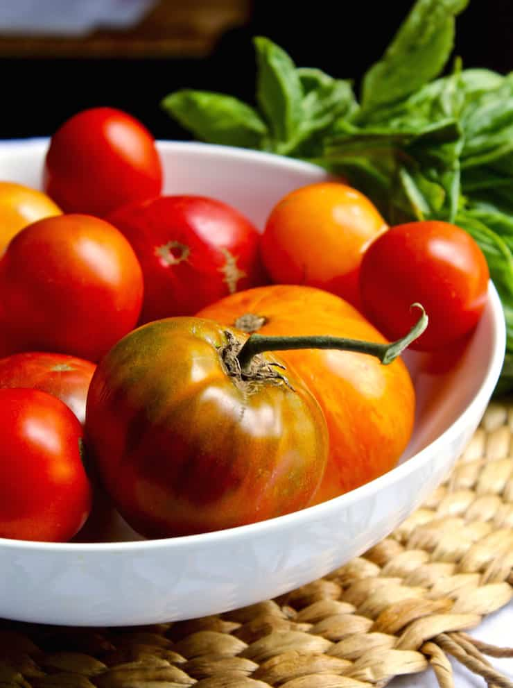 Bowl of summer tomatoes and fresh basil.