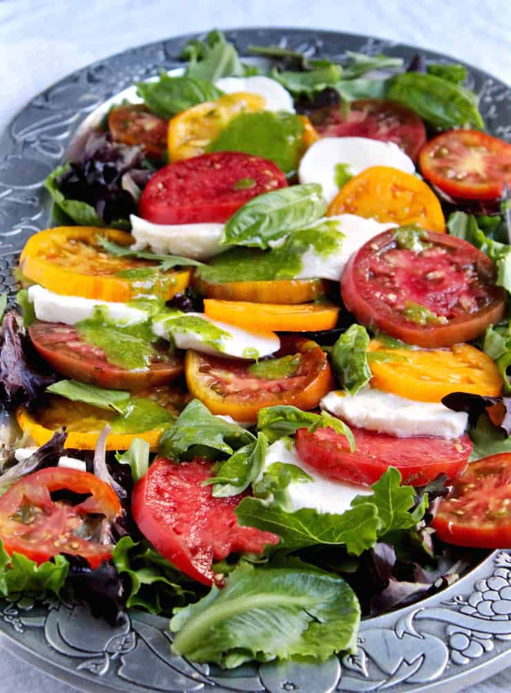 Close up of tomatoes and mozzarella with dressing arranged on platter.