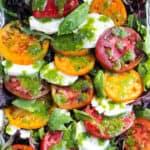 Insalata caprese with fresh mozzarella and basil dressing on serving platter.