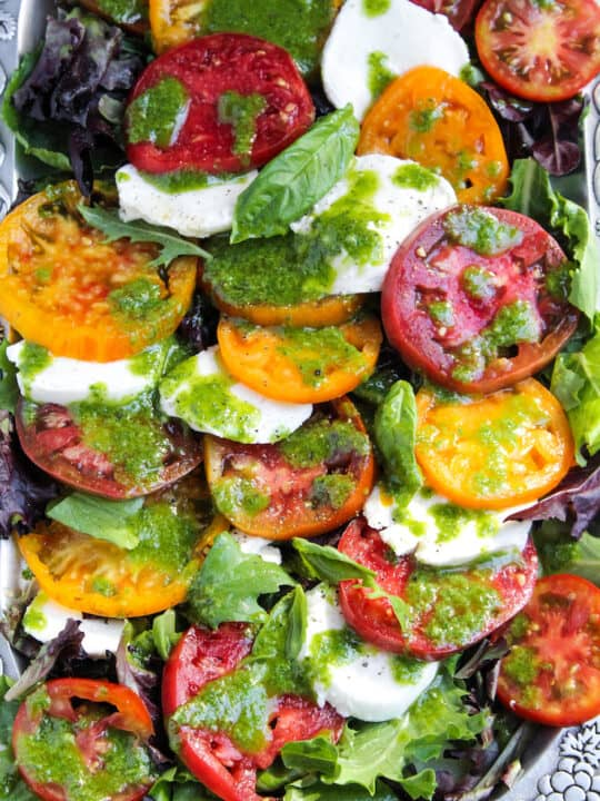 Insalata caprese with fresh mozzarella and basil dressing on serving platter.
