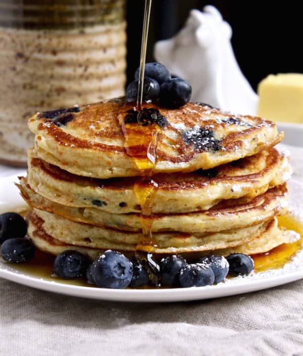 Cornmeal Blueberry pancakes, side photo of stack of pancakes with syrup being poured over them.