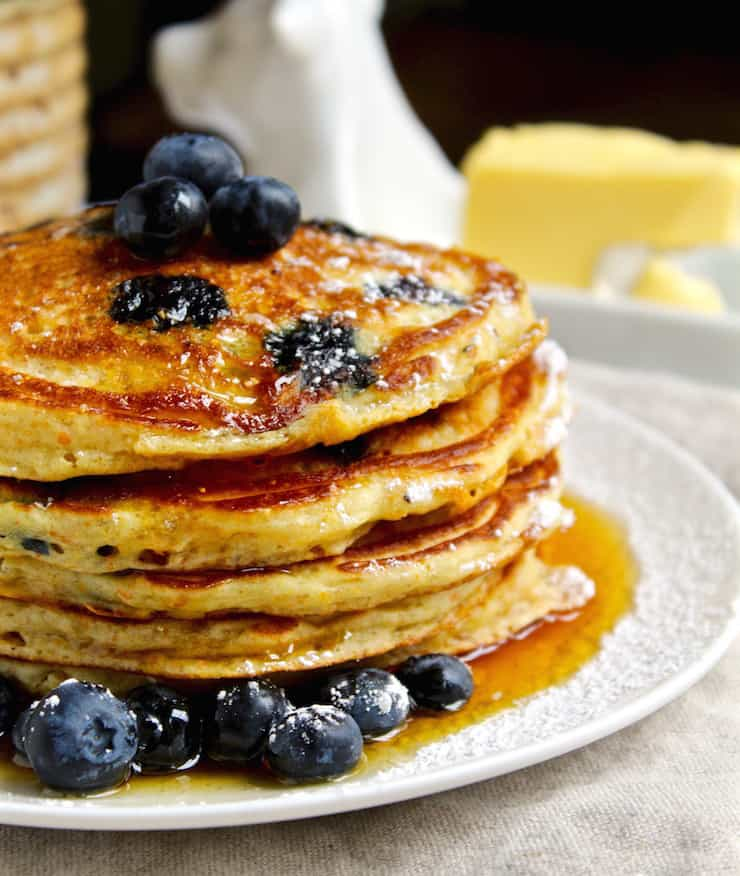 Cornmeal Blueberry Pancakes, side view of stack of pancakes with butter and syrup.