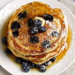 Cornmeal Blueberry Pancakes, overhead shot on plate with butter and syrup