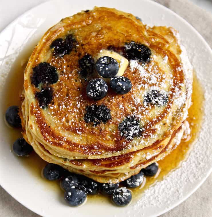 Cornmeal Blueberry Pancakes, overhead shot on plate with butter and syrup.