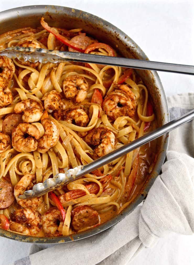 Creamy Cajun Shrimp Pasta with Sausage in skillet with tongs